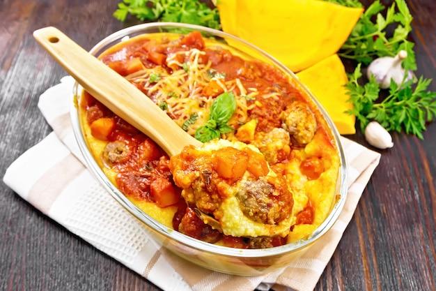 ミートボール、トマト、カボチャとチーズ、バジルとスプーンを乗せたタオルに乗ったトウモロコシのお粥