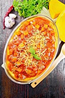 ミートボール、トマト、カボチャ、チーズの入ったコーンのお粥、タオル、ボードの背景、