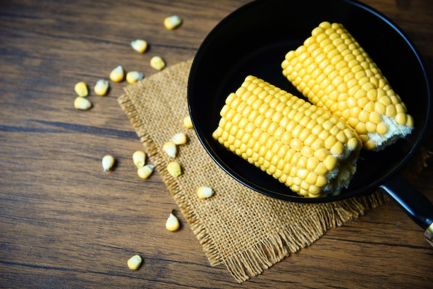 Corn on pot pan for cooking sweet corn ears on wooden
