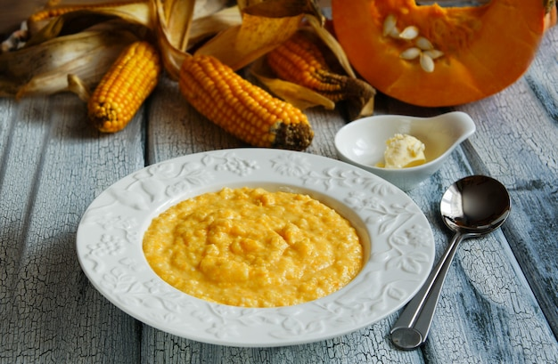 Corn pumpkin  on the white plate with butter
