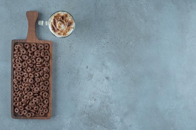Anello di mais in una tavola accanto a un bicchiere di caffè al latte, sullo sfondo blu.
