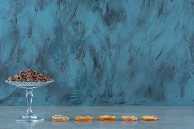 파란색 배경에 레몬 조각 옆 유리 받침대에 옥수수 반지.