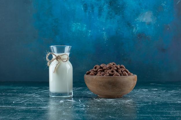 Anelli di mais in una ciotola accanto a una brocca di latte, sullo sfondo blu. foto di alta qualità