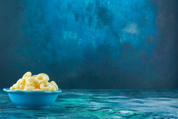 青いテーブルの上に、ボウルにトウモロコシが鳴ります。