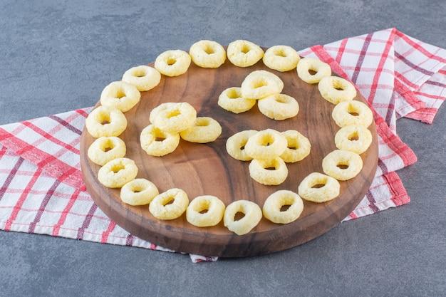 Кукурузные кольца на доске, на кухонном полотенце, на мраморной поверхности