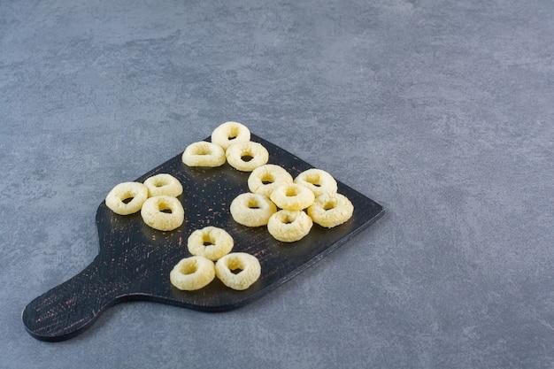 Кукурузные кольца на разделочной доске, на мраморной поверхности