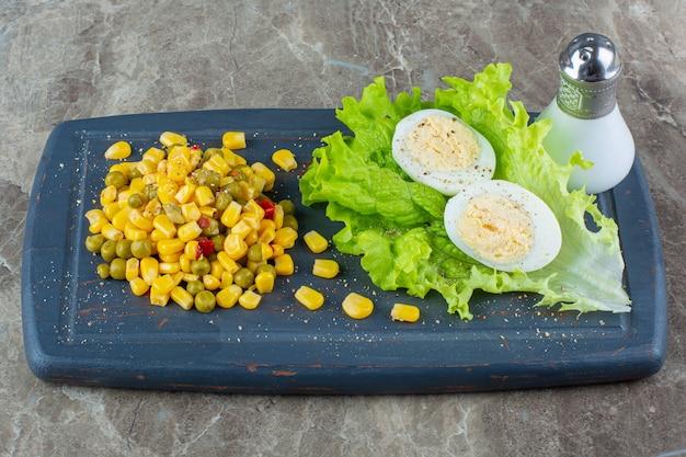Insalata di mais accanto all'uovo a fette su una lattuga su un vassoio, sulla superficie di marmo.