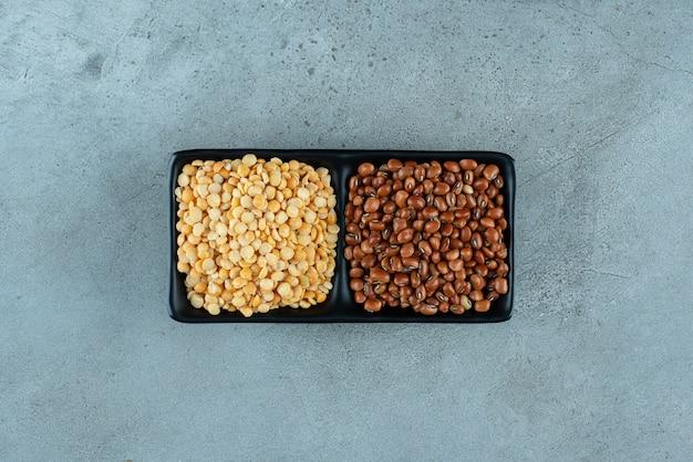 木製の大皿にトウモロコシの種と茶色の豆。高品質の写真