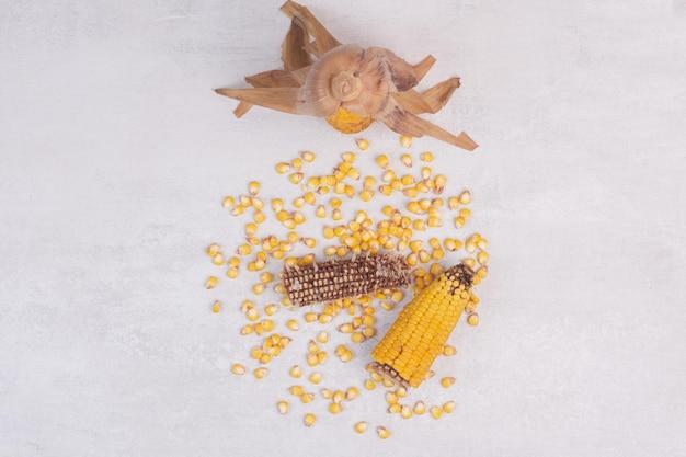 흰색 테이블에 옥수수 씨앗과 반 삶은 옥수수.