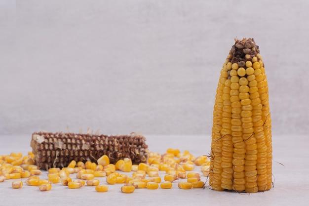 Semi di mais e mais mezzo bollito sul tavolo bianco.