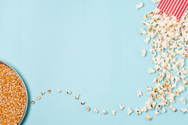 青い背景上のボックスからこぼれたポップコーンプレート上のコーンの種子