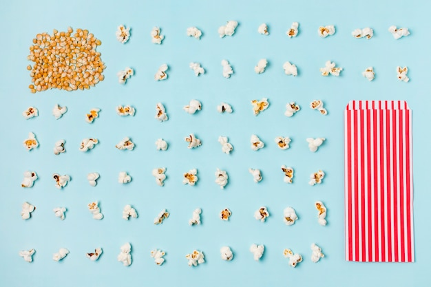 Corn seeds and row of popcorns with stripped popcorn box against blue backdrop