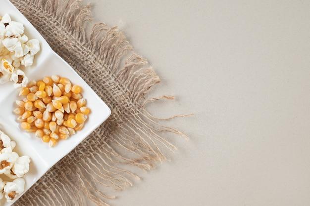 Semi di mais con popcorn in un piatto bianco.