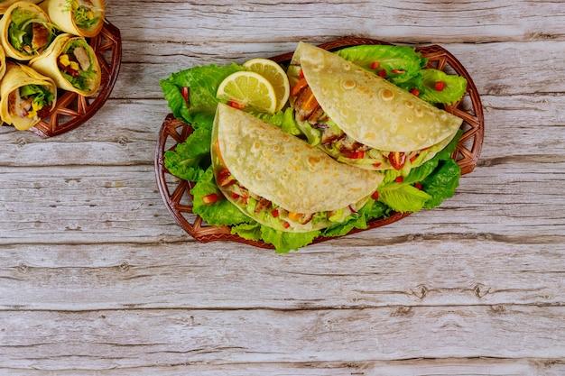 Кукурузные лепешки мягкие, фаршированные листьями салата, мяса и сыра на деревянных фоне. мексиканское блюдо