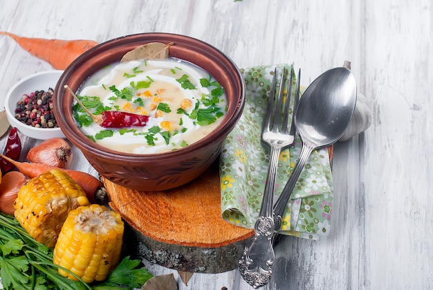 Corn soup in a ceramic plate and ingredients