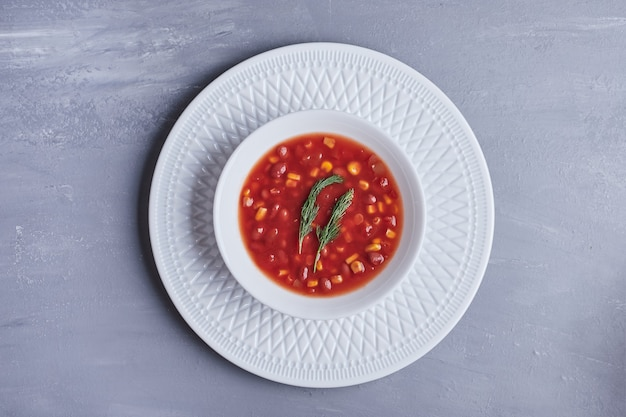 白いボウルにトマトソースのコーンスープ。