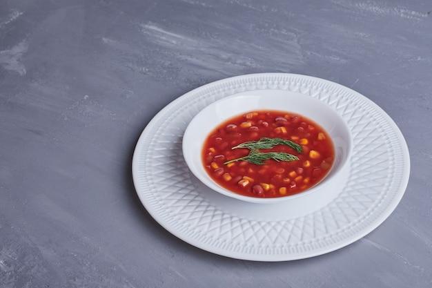 Кукурузный суп в томатном соусе в белой тарелке.