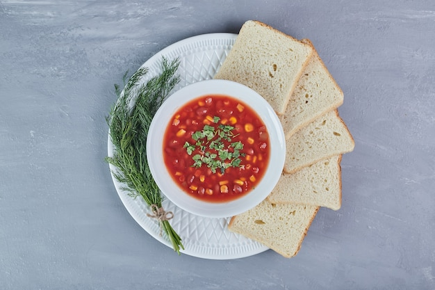 Corn soup in tomato sauce in a white plate with herbs.