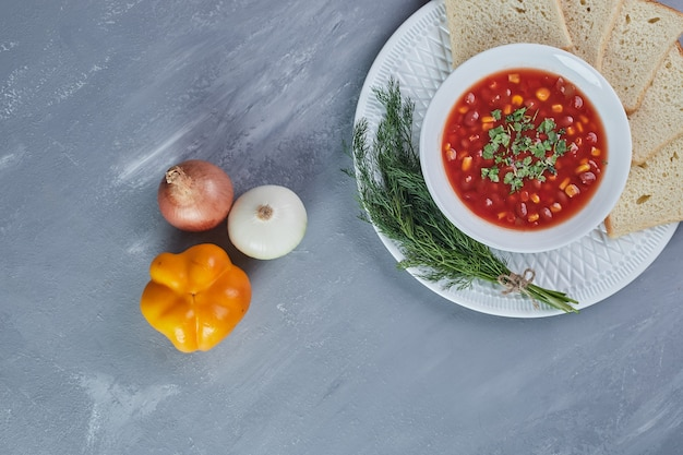 Corn soup in tomato sauce with bread.