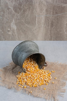 Corn spliing out of a small metal jug fallen over on a piece of cloth on marble surface