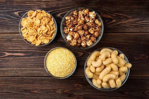 Кукурузные палочки, кукурузные хлопья и попкорн на темном деревянном фоне.