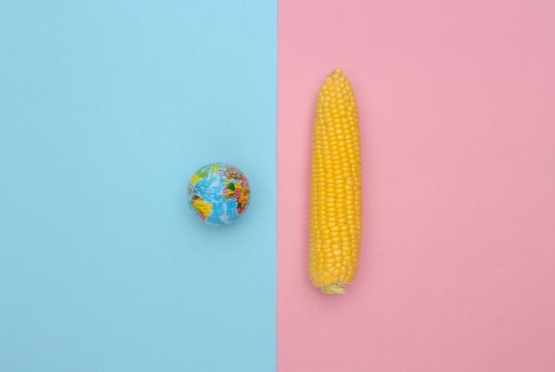 핑크 블루 파스텔 배경에 옥수수 스윙과 글로브. 행성을 저장합니다.