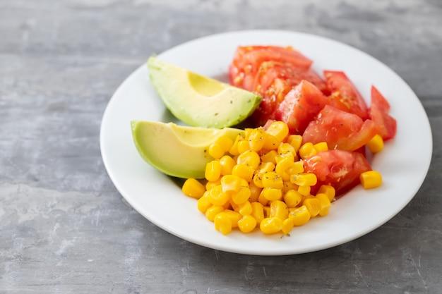 セラミック背景の白いプレートにトウモロコシ、トマト、アボカドのサラダ