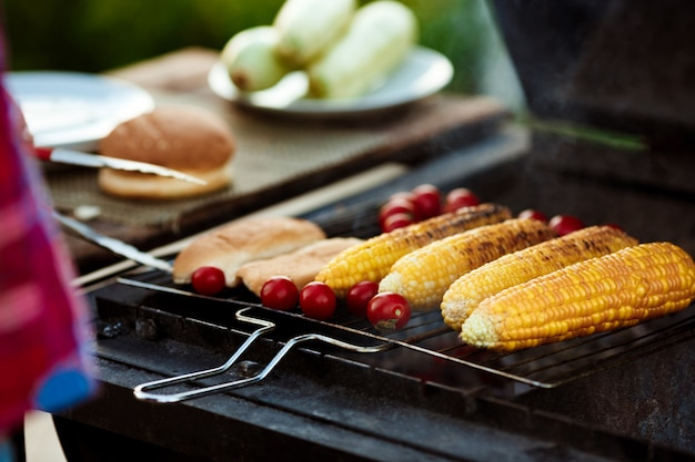Corn, tomatoes on grill. barbecue party.