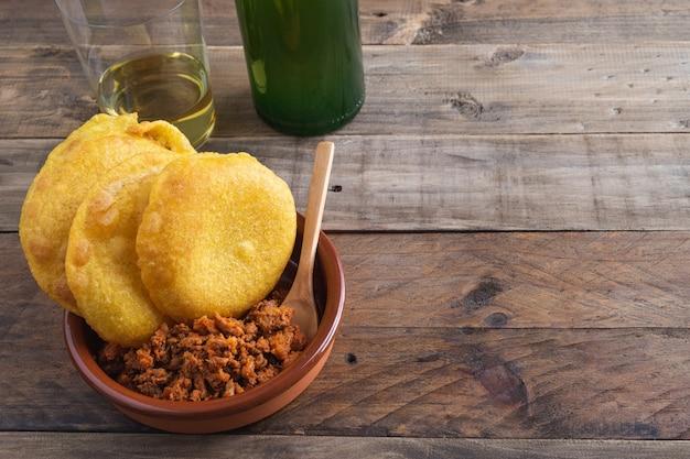 피카 딜로와 계란 후라이를 곁들인 옥수수 토르 토. 아스투리아스 사이다 병과 유리. 전형적인 아스투리아스 요리. 공간을 복사하십시오.