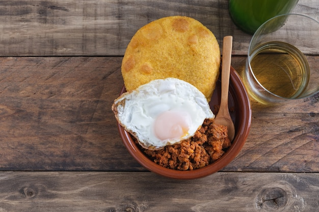 Corn tortos with picadillo and fried egg on a wooden base. typical asturian cuisine.