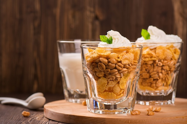 Corn and wheat flakes in glasses, served with milk, cream and mint on wooden table.
