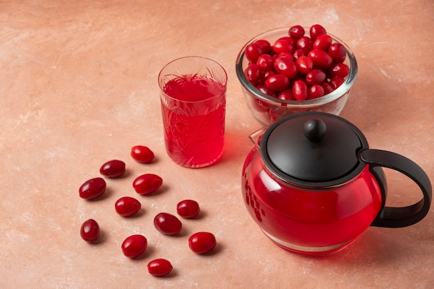 Cornel berries in the cup and juice in the kettle.