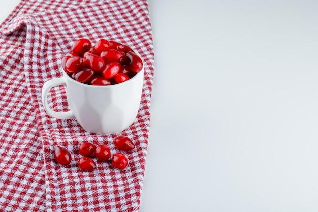 ピクニック布と白のカップでコーネルベリー。ハイアングル。