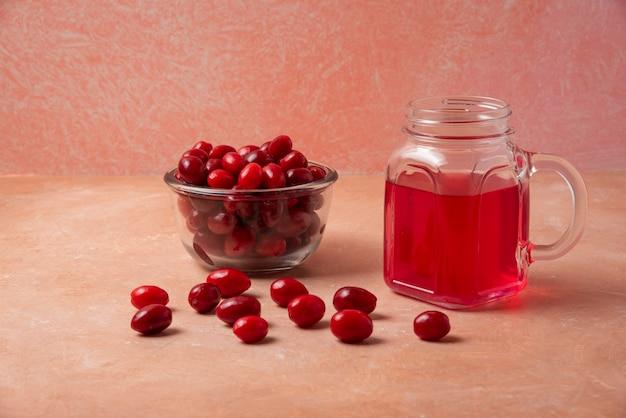 Ягоды кизила в стакане и сок в стеклянной банке.