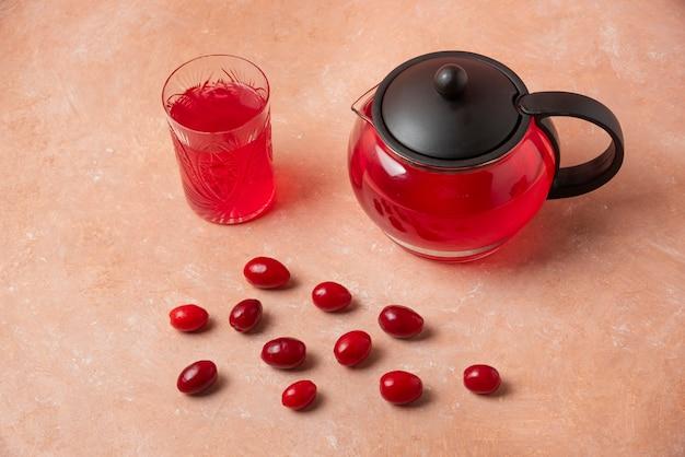Ягоды кизила в чашке и сок в чайнике.