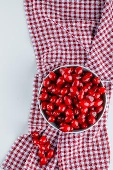 Bacche di corniolo in una vista dall'alto del piatto sul panno bianco e da picnic