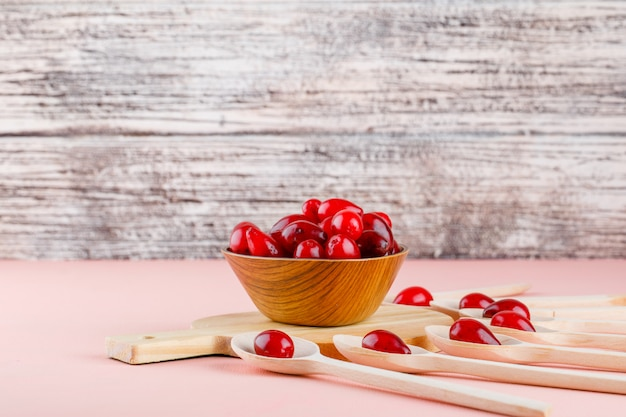 Cornel berries in spoons and bowl with cutting board side view on pink and wood