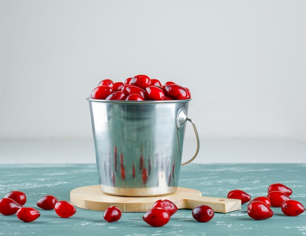 Cornel berries with cutting board in a bucket on plaster and white, side view.