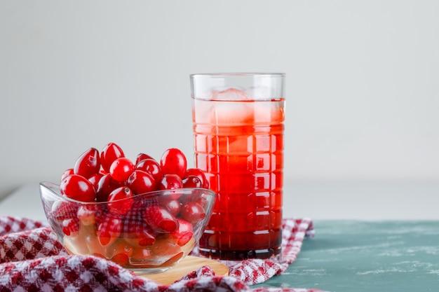 Ягоды кизила с напитком, разделочная доска, ткань для пикника в миске на гипсе и белом, вид сбоку.