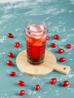 Ягоды кизила с напитком под высоким углом на гипсе и разделочной доске