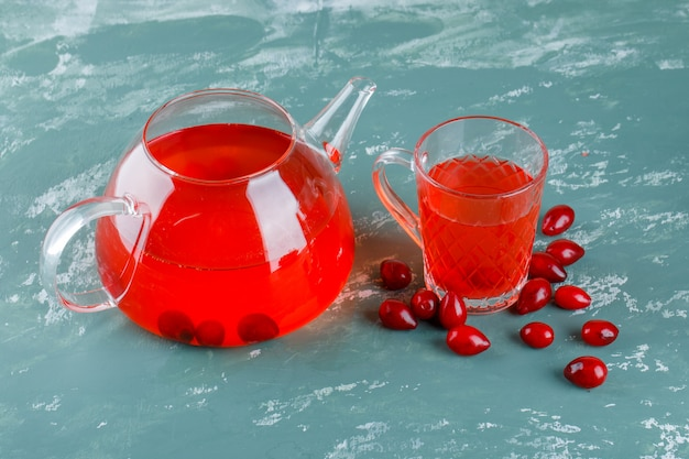 Cornel berries with drink high angle view on plaster