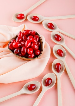 Cornel berries in wooden spoons and bowl on pink and textile, high angle view.