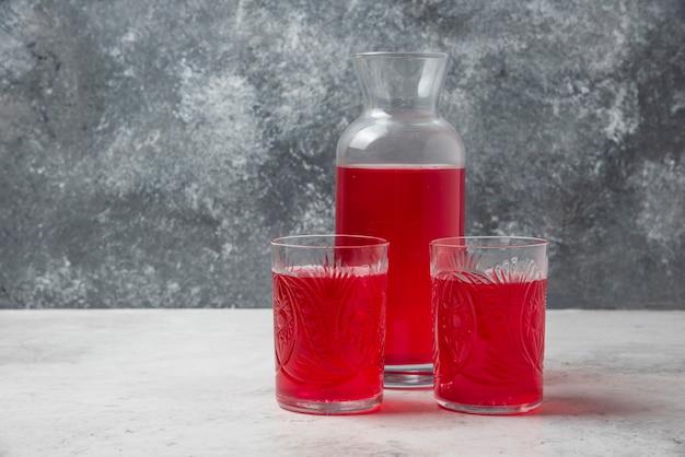 Cornel juice in glasses and jar.