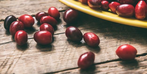 木製のテーブルのボウルにコーネリアンチェリーハナミズキ食用フルーツ