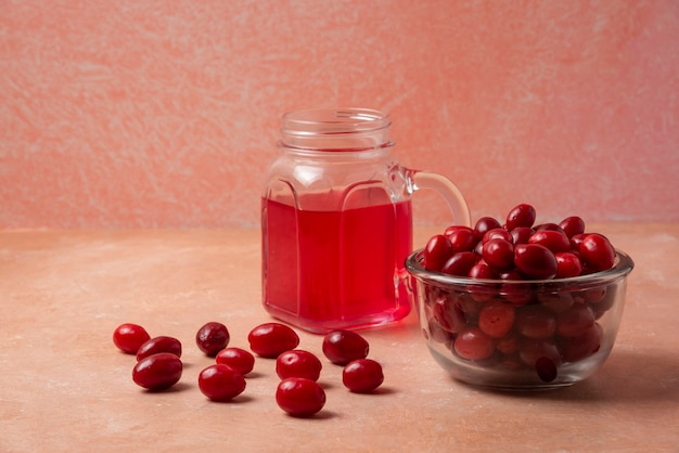 Cornels in glass cup on a pink background.
