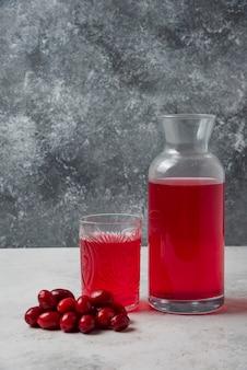 Cornioli con succo nel bicchiere e barattolo.