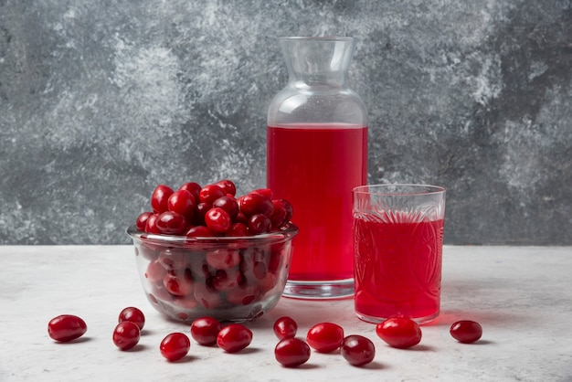 Cornels with juice in the glass and jar.