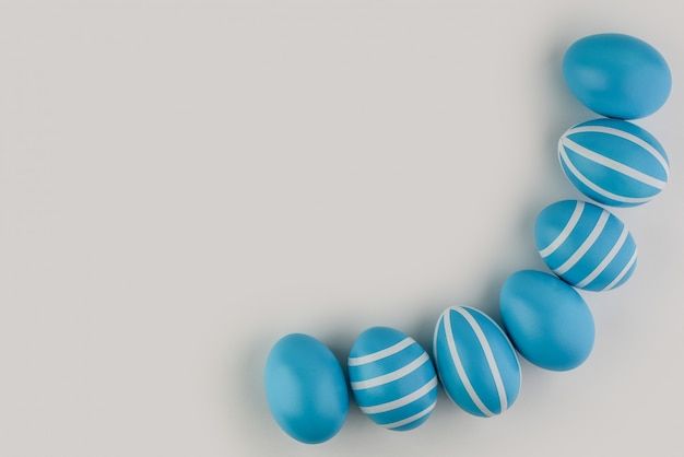 Corner border of blue striped easter eggs over a light background. shape of border frame corner with copy space for text content. happy easter card. top view, flat lay.