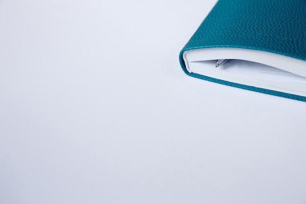 Угловая обложка синего блокнота, дневника или книги с ручкой на фоне белой бумаги