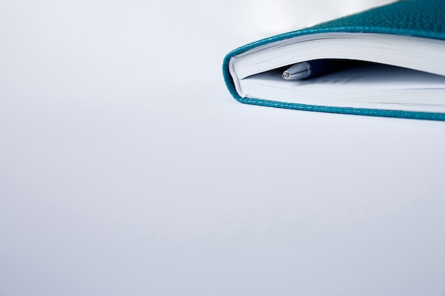 青いノート、日記、または白い紙にペンで本のコーナーカバー